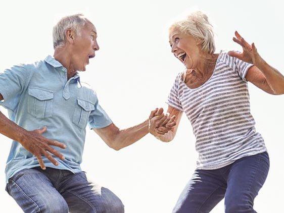 Senior Couple Bouncing On Trampoline In Garden